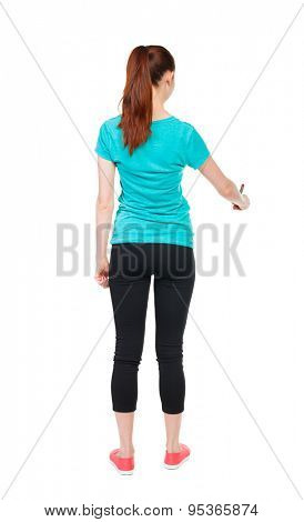 back view of writing beautiful woman. Young girl in sweatpants. Rear view people collection. backside view person. Isolated over white background. Sports girl draws felt-tip pen at bottom of something