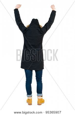 Back view of Beautiful woman in parka looking at wall and Holds  hand up.  young blonde girl standing.  The tall girl in a black warm jacket with a hood placed over the head gleefully waving his arms.