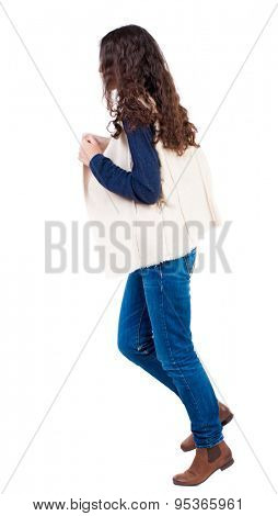 back view of running  woman. beautiful girl in motion. backside view of person.  Rear view people collection. Isolated over white background.Girl in sheepskin jerkin Runs left.