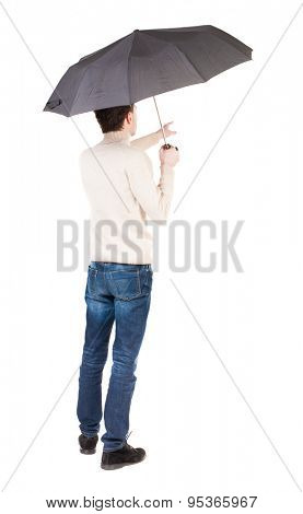 Back view of man in jeans under an umbrella. Standing young guy. Rear view people collection. A guy in a white warm sweater hiding from the rain under an umbrella and points vnebo.
