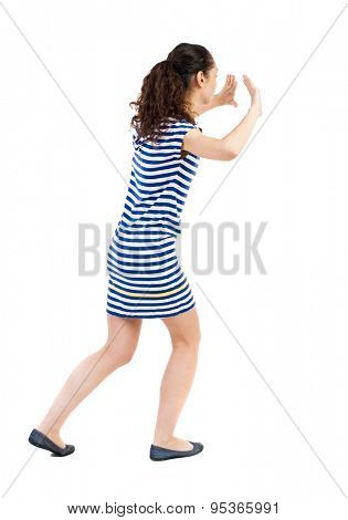 back view of woman pushes wall. Isolated over white background. Rear view people collection. backside view of person. African-American woman in a striped dress in barely pushes something on my own.