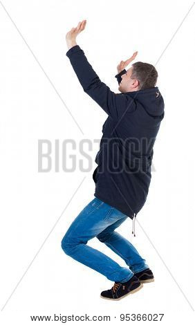 Balancing young man in parka.  or dodge the falling man. Rear view people collection.  backside view of person.  Isolated over white background. Sitting man trying to keep something on yourself.