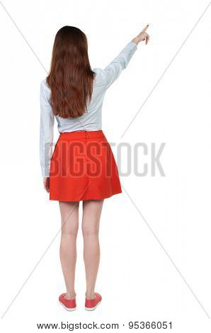 Back view of  pointing woman. beautiful girl. Rear view people collection.  backside view of person.  Isolated over white background. girl in red short skirt shows a finger sideways.