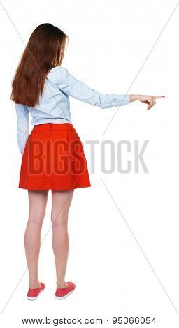 Back view of  pointing woman. beautiful girl. Rear view people collection.  backside view of person.  Isolated over white background. girl in red short skirt shows a finger to the side.