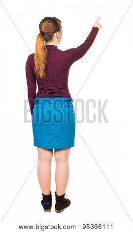 Back view of  pointing woman. beautiful girl. Rear view people collection.  Isolated over white background.  Girl in blue skirt is turning away from the viewer, and indicates where that finger.