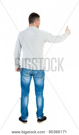 Back view of  man in shirt shows thumbs up.   Rear view people collection.  backside view of person.  Isolated over white background.  A guy in a gray jacket showing thumbs up with his right hand.