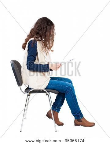 back view of young beautiful  woman sitting on chair.  girl  watching. Rear view people collection. Isolated over white background. Girl in sleeveless sheep sits on a chair and reading a document.