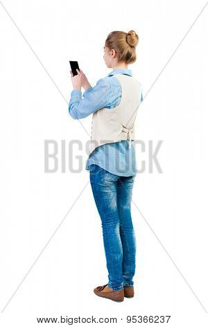 back view of standing young beautiful  woman  in vest and using a mobile phone. girl  watching. R Isolated over white background. Girl in sleeveless finger presses the screen of the mobile phone.