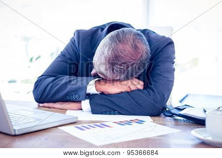 Businessman resting head on desk in his office
