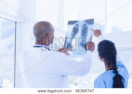 Doctors analyzing together xray in medical office
