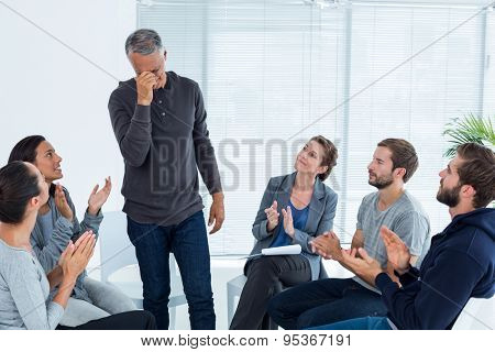 Rehab group applauding delighted man standing up at therapy session
