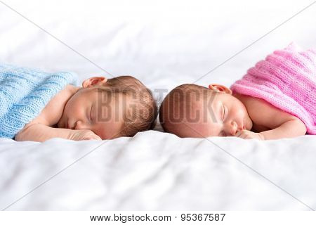Boy and girl twins lying down in bed