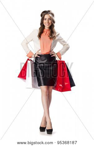 Full length portrait of a beautiful young brunette woman posing with shopping bags, isolated on white background