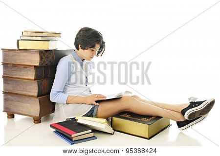 An attractive young teen reading one of the books that surround her.  On a white background.