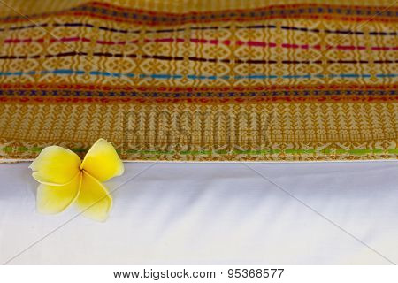 Traditional indonesian woven bed cover over the white sheet, decorated with plumeria flower