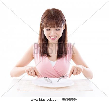 Asian girl eating with fork and spoon, empty plate ready for food. Young woman living lifestyle.
