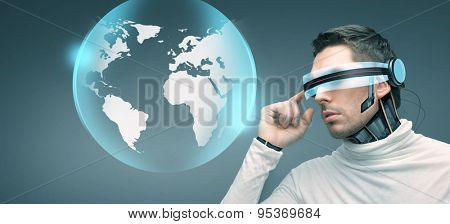 people, technology, future and progress - man with futuristic 3d glasses and microchip implant or sensors over blue background and earth globe hologram