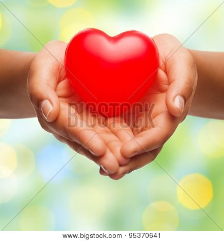 health, medicine, love, valentines day and charity concept - close up of african american female hands holding small red heart over green lights background