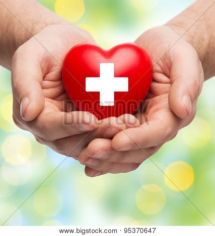 family health, charity and medicine concept - close up of male hands holding red heart with white cross over green lights background