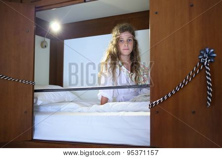 Girl with long hair and white blouse sitting on the bed