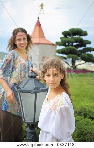 Mother and daughter in ethnic dress near the medieval castle, focus on girl