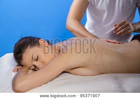 Professional masseur doing massage on woman body in the spa salon. Beauty treatment concept.
