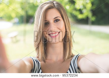 Beautiful young woman making selfie and grimacing