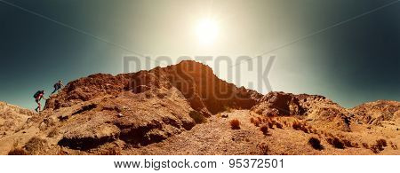 Two hikers climbing the mountain in the desert