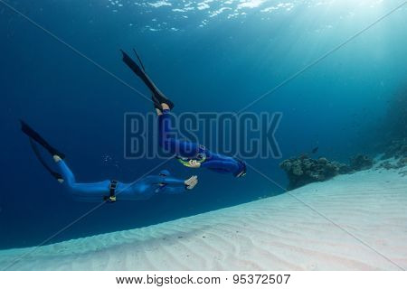 Two freedivers finning over the sandy sea bottom