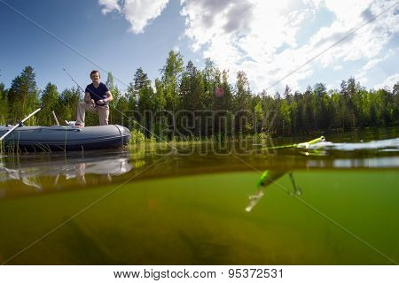 Young man fishing on the fresh water pond with surface floating bait