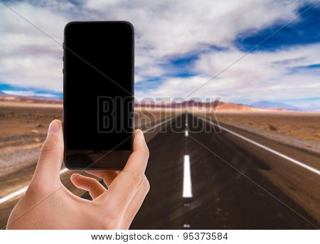 Hand holding mobile smart phone with black screen with desert road on background