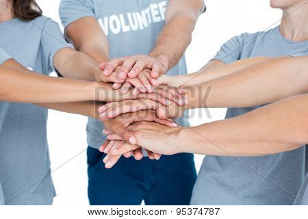 Happy volunteers friends putting their hands together