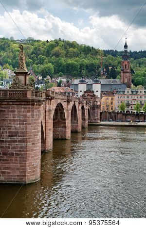 Looking Across Neckar River at Old Bridge Leading to Old Town Heidelberg, Baden-Wurttemberg, Germany with Clouds Overhead