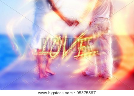 Beautiful love couple standing barefoot holding hands on a jetty by the sea in the Maldives with a dreamy surreal effect and word - Love - in fiery letters, symbolic of romance and commitment