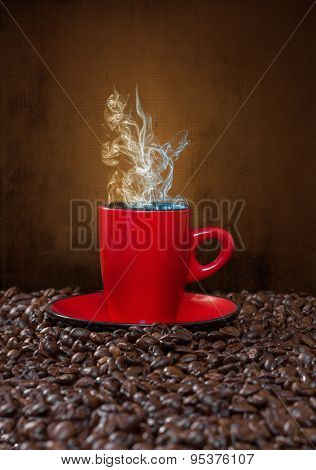Red cup of coffee with steam on a background of coffee beans.