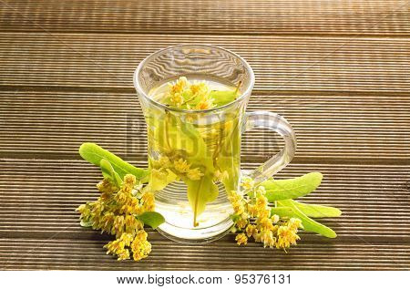 Glass of tea with linden flowers on a wooden background