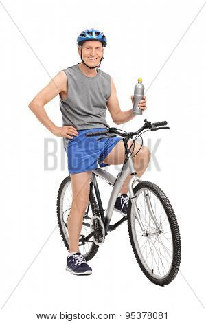 Full length portrait of a senior man with a blue helmet holding a water bottle and posing seated on his bike isolated on white background