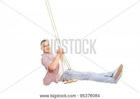 Profile studio shot of a delighted young man swinging on a wooden swing and looking at the camera isolated on white background
