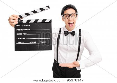 Young movie director holding a clapperboard in one hand and pointing towards it with the other isolated on white background