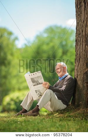 Senior man reading a newspaper in park and leaning against a tree. The newspaper is custom made the pictures are my copyright.