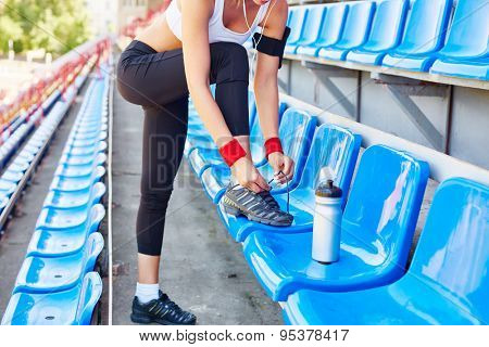 Modern girl with iphone tying shoelaces on her sports-shoes at stadium