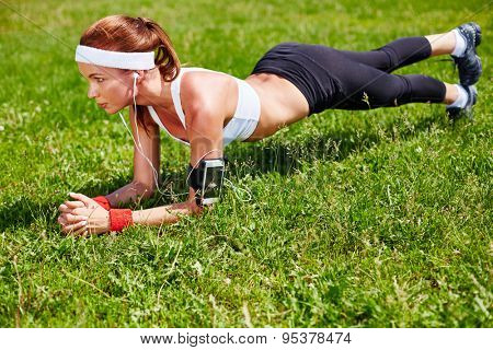 Sporty girl practicing pushups on green grass