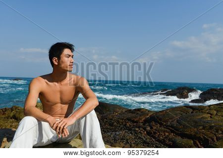 Yong muscular man sitting on a marine cape at the evening
