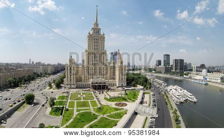 RUSSIA, MOSCOW - JUN 6, 2014: Hotel Ukraine on quay of river with vessels, skyscraper complex of Moscow Business Center at summer sunny day. Aerial view. Photo with noise from action camera