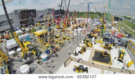 RUSSIA, MOSCOW - JUN 6, 2014:  People walk by International Specialized Exhibition of Construction Equipment and Technologies CET 2014 at Crocus Expo. Photo with noise from action camera