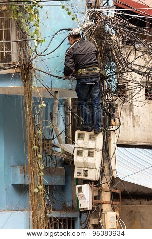 HANOI, VIETNAM, DECEMBER 16, 2014 : A technician standing on the electricity meters is repairing or checking the messy electrical network in the city of Hanoi, Vietnam