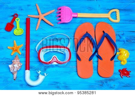 high-angle shot of a rustic blue wooden table full of summer stuff, such as some starfishes, a conch, a diving mask and a snorkel, a pair of flip-flops and some beach toys