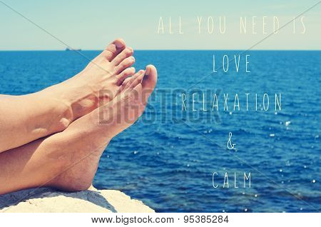closeup of the bare feet of a young Caucasian man relaxing on the sea and the text all you need is love and relaxation and calm