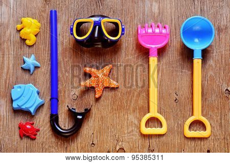 high-angle shot of a rustic wooden table full of summer stuff, such as a starfish, a diving mask and a snorkel and some beach toys, such as shovels and sand molds