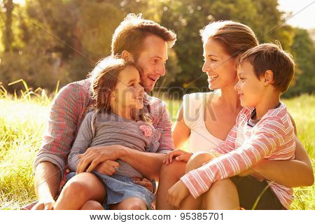 Family relaxing together outdoors, looking at each other